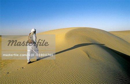 Egypt, Libyan desert, Beduin walking on a sand dune