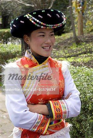 China, Yunnan, near Kunming, Yunnan Nationalities Village, young woman wearing traditional costume