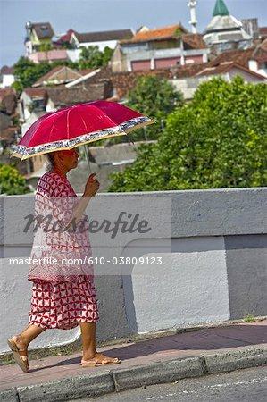 Indonesia, Java, Yogyakarta, old woman with an umbrella