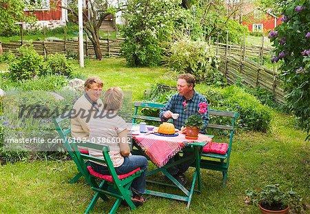 A farmer family having a coffee in the garden, Sweden.