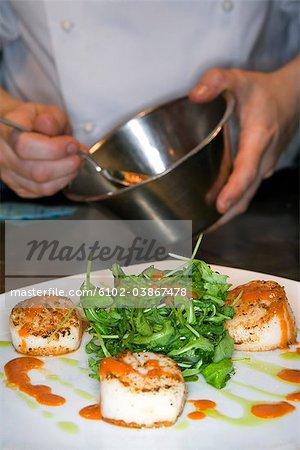 A cook preparing food in a restaurant kitchen, Sweden.