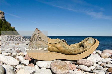 Old damaged shoe on stone beach