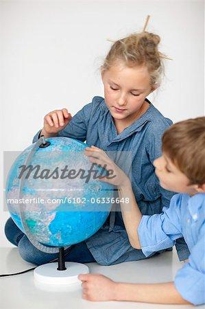 Boy and girl reading globe