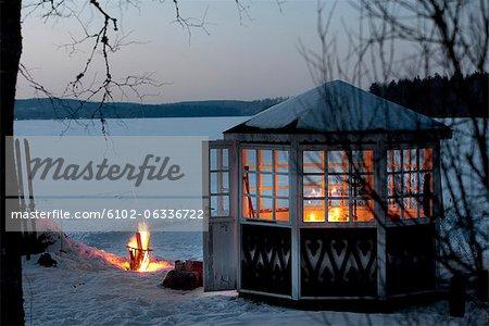 Fire in front of gazebo on snowy landscape