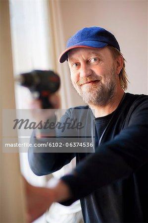 Portrait of smiling man drilling