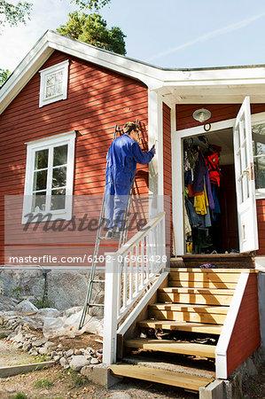 Young man repairing facade