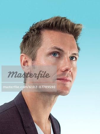 Portrait of young man looking away, studio shot