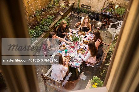 Teenage girls having meal on courtyard