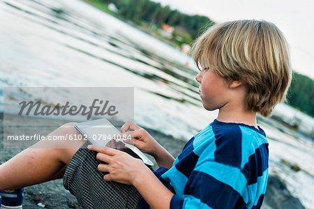 Boy using digital tablet at water