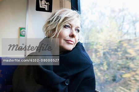 Mature woman looking through window in train