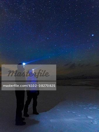 Men looking at stars on sky