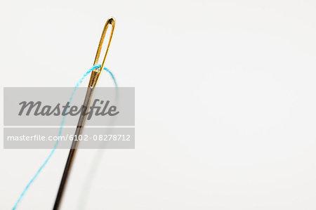 Sewing needle with blue thread through eye