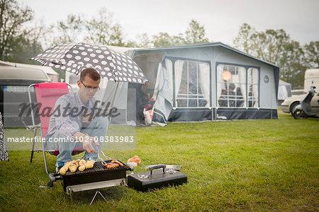 Man barbecuing in rain