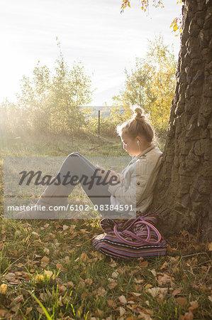 Girl sitting under tree and listening music