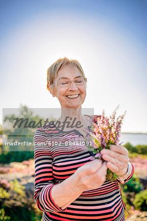 Senior woman holding wildflowers