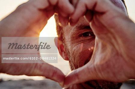 Portrait of man making heart-shape on beach