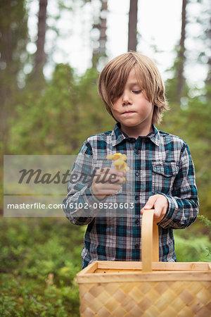 Boy holding mushroom and basket