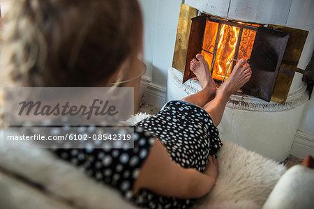 Woman warming feet by fireplace
