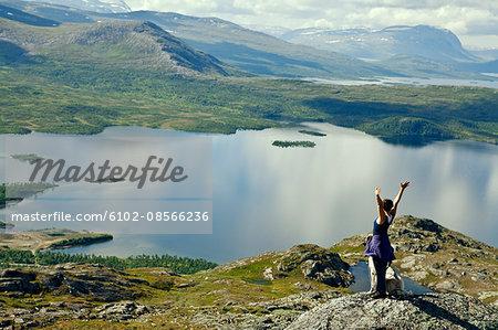 Tourist on top of rock overlooking lake