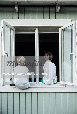 Boys sitting on window