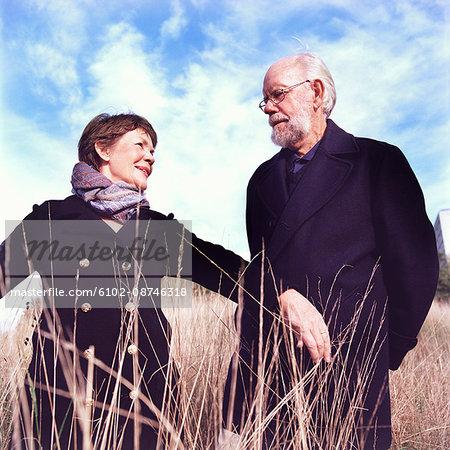 Portrait of senior couple standing on field