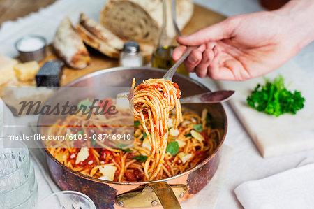 Hand holding spaghetti on fork