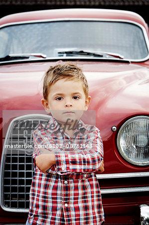 Boy in front of vintage car, Stockholm, Sweden