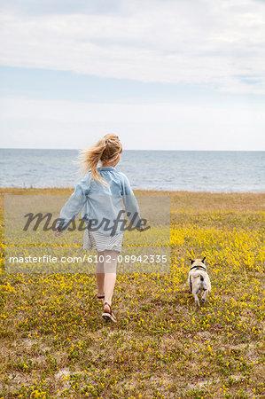 Girl walking with dog at sea