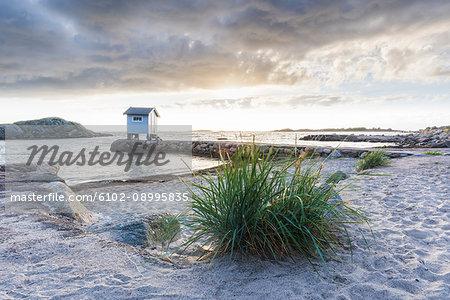 Sandy beach, wooden building on background