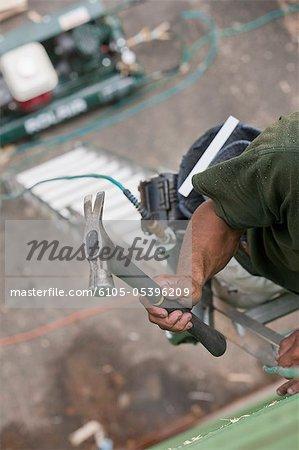 Hispanic carpenter climbing ladder with hammer and nail gun at a house under construction