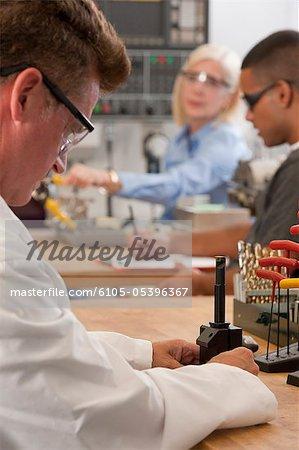Engineering professor installing CNC machine tool in the tool holder