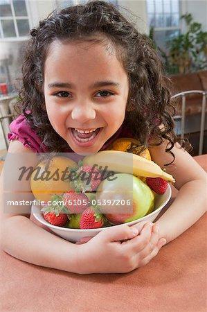 Hispanic girl picking up bowl of fresh fruits