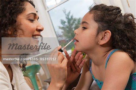 Hispanic woman applying lipstick on her daughter's lips