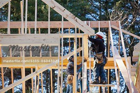 Carpenters using a nail gun on dormer framing