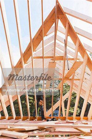 Carpenter standing on joist of roof under construction