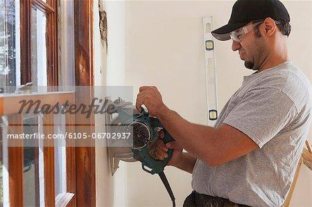 Hispanic carpenter using circular saw to cut wallboard for deck doorway in house