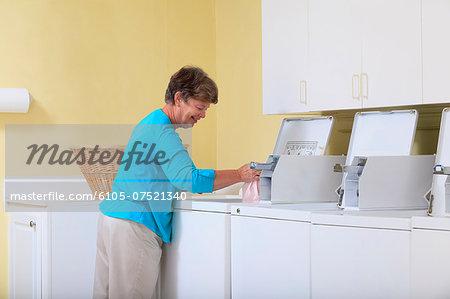 Senior woman putting laundry in a washing machine