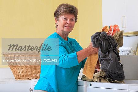 Senior woman doing laundry in a washing machine