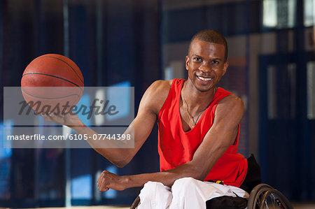 Man who had Spinal Meningitis in wheelchair holding basketball