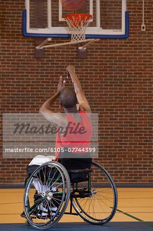 Man who had Spinal Meningitis in wheelchair taking a net shot in basketball