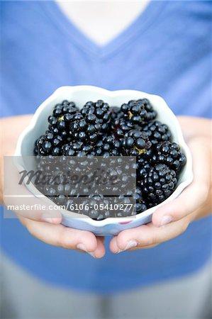 Girl holding bowl of freshly picked black berries