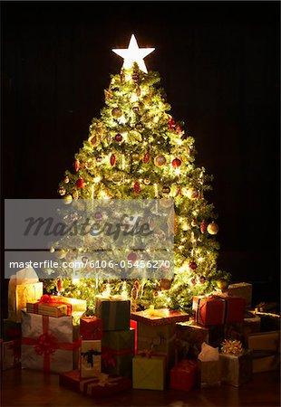 Presents around lit Christmas tree