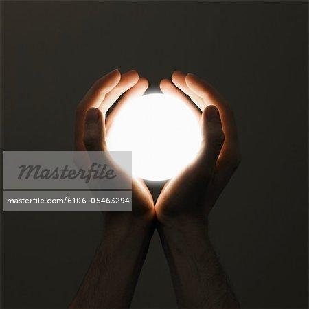 Hands holding orb of light, close-up, (digital enhancement)