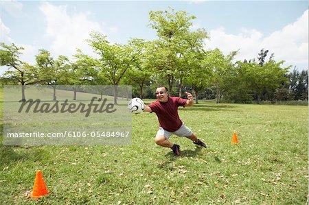 Man diving for soccer ball in goal, smiling