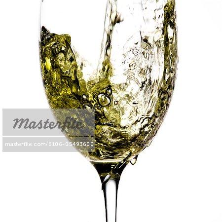 Pouring white wine into wineglass