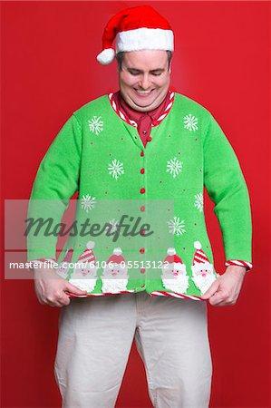 Man wearing Christmas sweater, smiling, studio shot