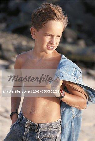 Boy (6-7) carrying shirt on beach, close-up