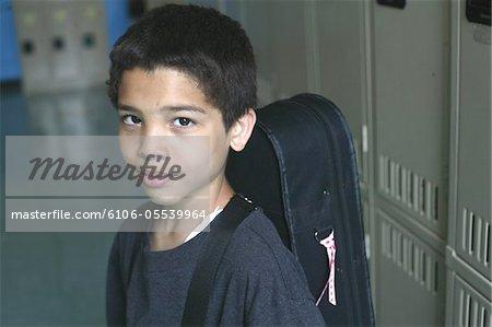 Boy (9-11) standing near school lockers, guitar on shoulder, portrait