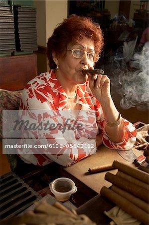 Senior woman smoking cigar in cigar factory, portrait