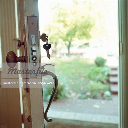 open front door. Open Front Door Of House, Key In Keyhole - Stock Photo